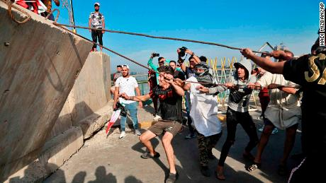 Anti-government protesters pull down concrete walls leading to the heavily guarded Green Zone.