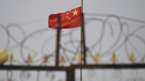 TOPSHOT - This photo taken on June 4, 2019 shows the Chinese flag behind razor wire at a housing compound in Yangisar, south of Kashgar, in China