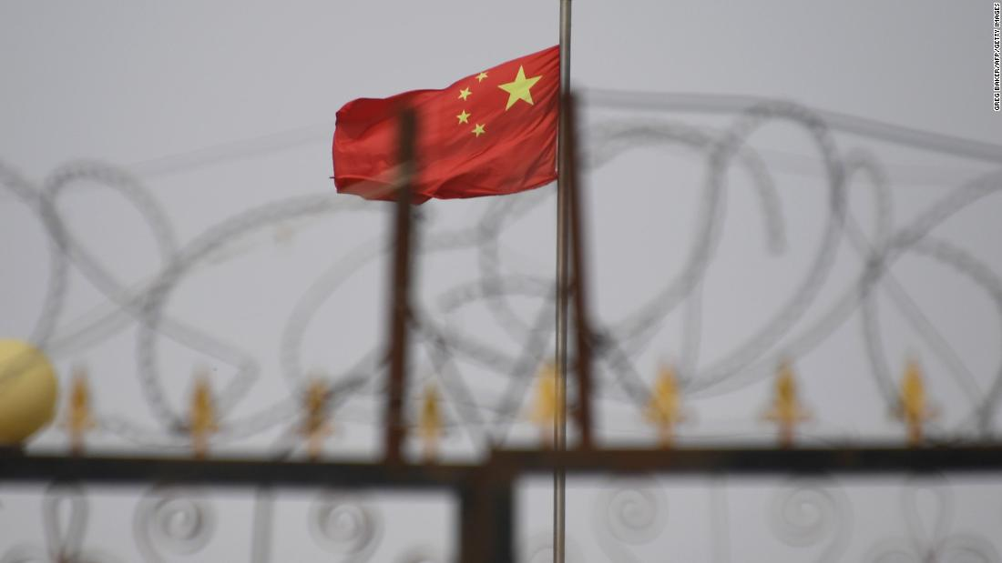 TOPSHOT - This photo taken on June 4, 2019 shows the Chinese flag behind razor wire at a housing compound in Yangisar, south of Kashgar, in China's western Xinjiang region. - A recurrence of the Urumqi riots which left nearly 200 people dead a decade ago is hard to imagine in today's Xinjiang, a Chinese region whose Uighur minority is straitjacketed by surveillance and mass detentions. A pervasive security apparatus has subdued the ethnic unrest that has long plagued the region. (Photo by GREG BAKER / AFP)        (Photo credit should read GREG BAKER/AFP/Getty Images)