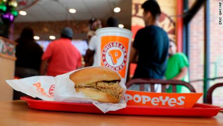 A chicken sandwich sits on a table at a Popeyes as guests wait in line.