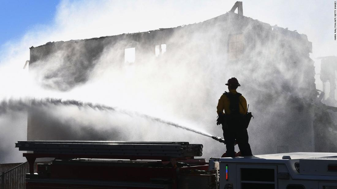 Firefighters hose down a burning house in Agua Dulce, California, on Friday, October 25. It was affected by the Tick Fire, which broke out near Santa Clarita.