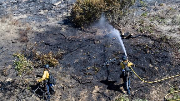 Orange County firefighters put out remaining hot spots from a brush fire in San Clemente, California, on October 25.
