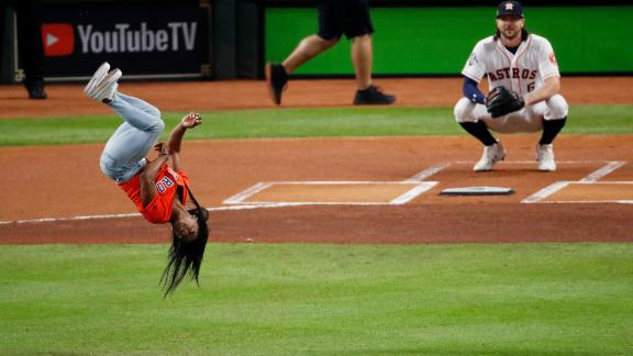 World champion gymnast Simone Biles performs a flip before throwing out the first pitch for Game 2.