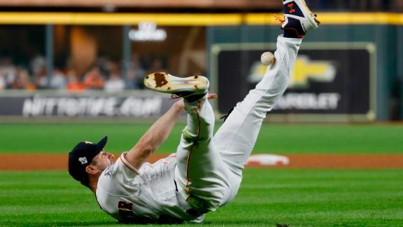 Houston pitcher Justin Verlander dives to the ground and tries to make a throw to first, but he hit his leg instead.