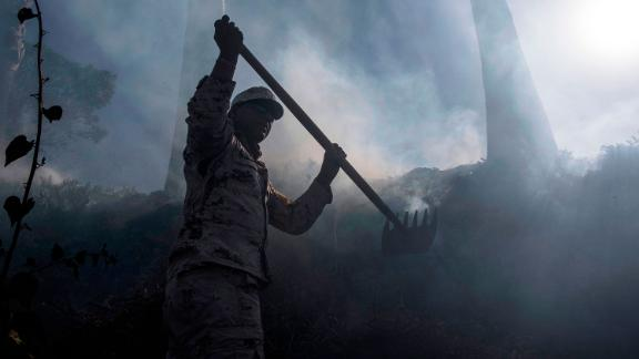 A Mexican soldier works to contain a brush fire on the outskirts of Tijuana in Baja California
