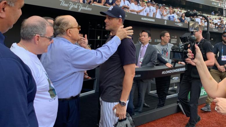 Rudy Giuliani (center) speaks with New York Yankees manager Aaron Boone prior to a game between the Yankees and the Boston Red Sox in London in June 2019.  Lev Parnas, a now-indicted associate of Giuliani's, can be seen standing on Giuliani's right.  Rudy Giuliani/Twitter