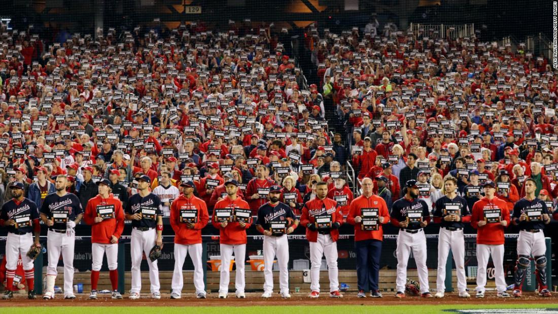 Fans, Funktionäre und Spieler nahmen eine kurze Pause von der World Series zu stehen bis zu Krebs
