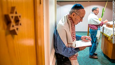 Joe Charny reads during a morning minyan prayer service at Congregation Beth Shalom.
