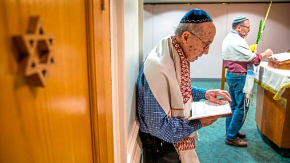Joe Charny, 91, a survivor from the Tree of Life shooting Oct. 27, 2018, reads during a morning minyan prayer service at Congregation Beth Shalom on Wednesday, Oct. 16, 2019, in the Squirrel Hill neighborhood of Pittsburgh. Since the Tree of Life synagogue shooting last year Beth Shalom has invited members of Tree of Life, New Light and Dor Hadash to join and lead their daily prayer service. (Andrew Rush/Pittsburgh Post-Gazette via AP)
