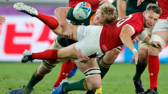 Wales' Dan Biggar passes the ball as he is tackled by Du Toit during the Rugby World Cup semifinal.
