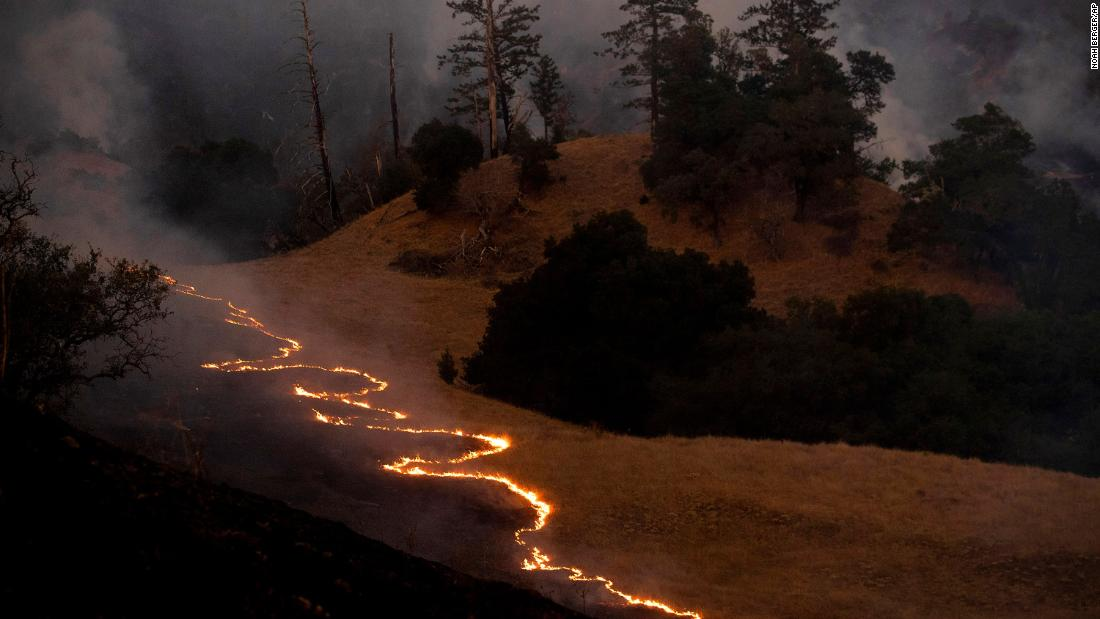 A line of fire snakes along a hillside as firefighters light backfires to slow the spread of the Kincade Fire near Geyserville, California, on October 26.