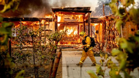 A firefighter passes a burning home as the Kincade Fire rages in Healdsburg on October 27.