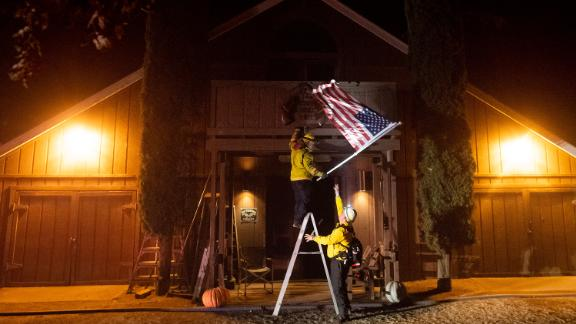 Firefighters from the Dry Creek Rancheria remove an American flag in Healdsburg.