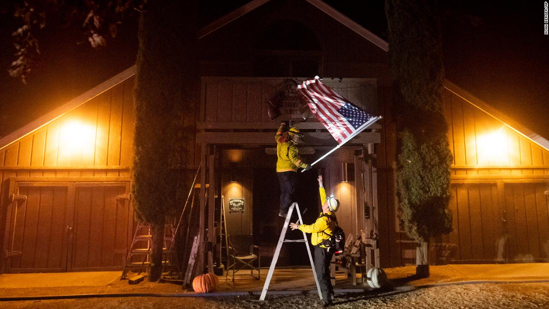 Firefighters from Dry Creek Rancheria remove an American flag in Healdsburg.