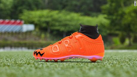 The neon orange cleat features Halloween-inspired designs.