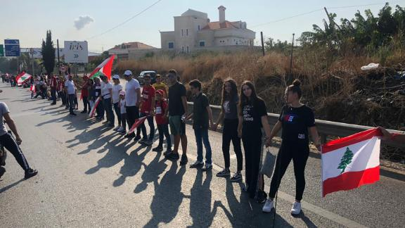 Lebanese men, women and children link arms to form a 105-mile human chain.