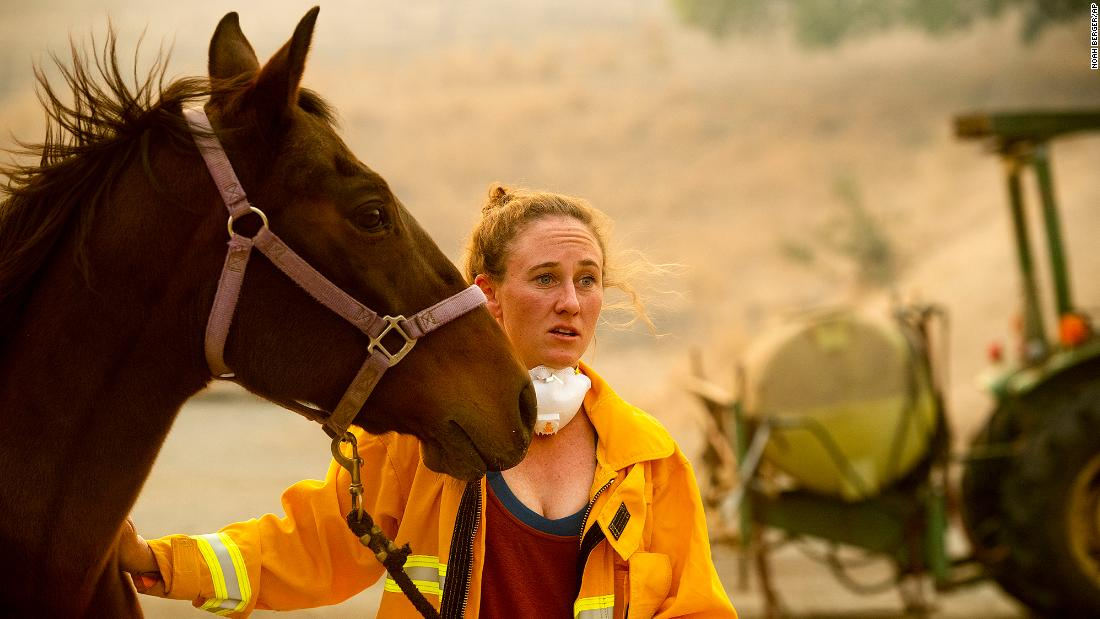 Dr. Emily Putt, a veterinarian who helps rescue horses from fire zones, comforts a horse as the Kincade Fire burns in Healdsburg on October 27.