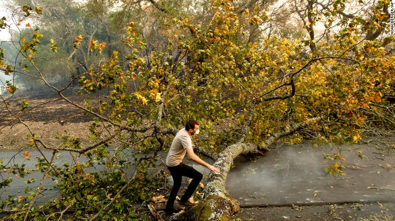 Brennan Fleming jumps a fallen tree while helping his girlfriend evacuate horses stranded by the Kincade Fire in Healdsburg, Caliornia on October 27.