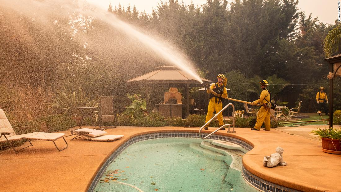 Firefighters battling the Kincade Fire spray water at a home in Windsor, California, on Sunday, October 27.