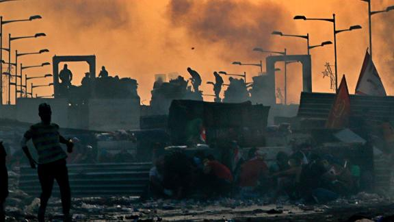 Anti-government protesters take cover while Iraqi security forces, back, fire tear gas and close the bridge leading to the Green Zone, during a demonstration at sunset in Baghdad, Iraq, Sunday, Oct. 27, 2019. Protests have resumed in Iraq after a wave of anti-government protests earlier this month were violently put down. (AP Photo/Khalid Mohammed)