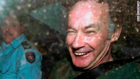 Ivan Milat smiles in a police car after attending a court in Sydney, Australia, on November 4, 1997.