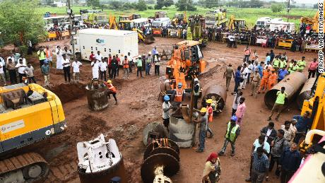 Rescue workers gather with heavy digging equipment during an operation to save a toddler trapped in a deep well in India's Tamil Nadu state.