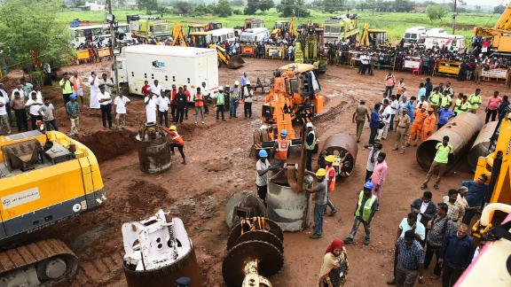 Rescue workers gather with heavy digging equipment during an operation to rescue a toddler stuck in a deep well.