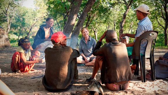 Hayes sits with Juǀ'hoansi hunters Nǂamce Sao, ǀkun Nǂamce and ǀkun ǀkunta (left to right).