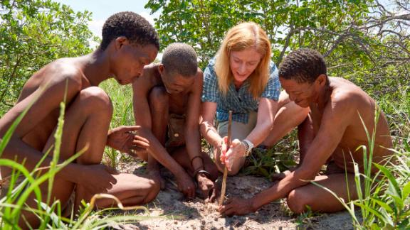 Professor Vanessa Hayes learning how to make fire with Ju?'hoansi hunters in the now dried homeland of the greater Kalahari of Namibia. From left to right: N?amce Sao, ?kun N?amce, Vanessa Hayes and ?kun ?kunta.