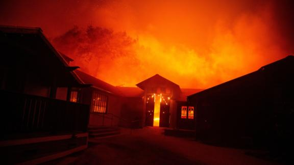 """The doors to the Soda Rock Winery burst open as it burns in Healdsburg, California on October 27, 2019. - Powerful winds were fanning wildfires in northern California in """"potentially historic fire"""" conditions, authorities said October 27, as tens of thousands of people were ordered to evacuate and sweeping power cuts began in the US state. (Photo by Josh Edelson / AFP) (Photo by JOSH EDELSON/AFP via Getty Images)"""