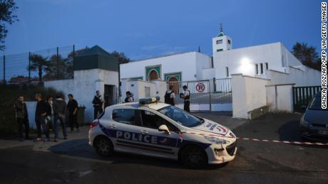 Police officers stand in front of the Mosque of Bayonne after two people were injured in a shooting.