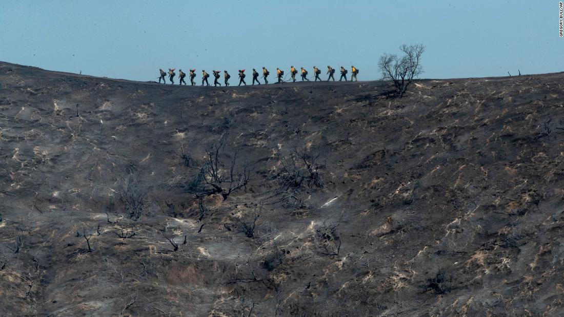 Fire crews walk along a blackened ridge as they battle the Getty Fire in Los Angeles.