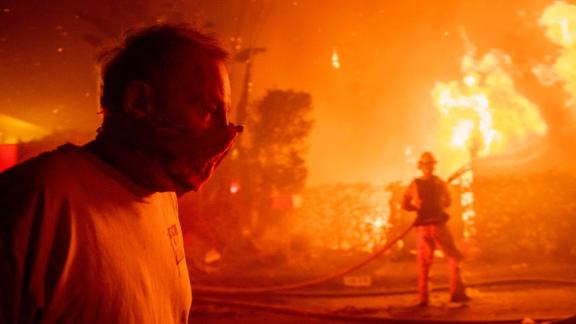 A man walks past a burning home in Los Angeles on October 28.