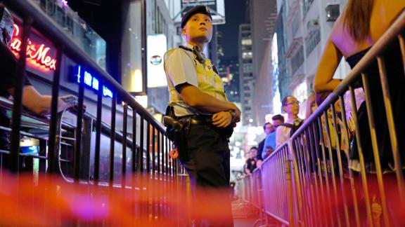 A police officer stands guard as people celebrate Halloween in Lan Kwai Fong in 2017.