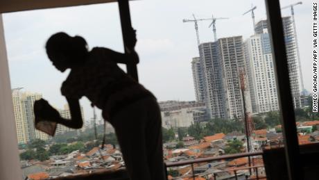 A house maid cleans an apartment window in Jakarta while a construction site for high rise commercial and residential buildings are seen in the background.