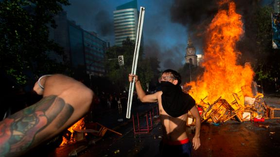 Demonstrators stand by a fire barricade during clashes with riot police outside La Moneda presidential palace, in Santiago, on October 28, 2019. - Chilean President Sebastian Pinera unveiled a major cabinet reshuffle on Monday as he battles to find a response to more than a week of street protests that have left at least 20 people dead. (Photo by CLAUDIO REYES / AFP) (Photo by CLAUDIO REYES/AFP via Getty Images)