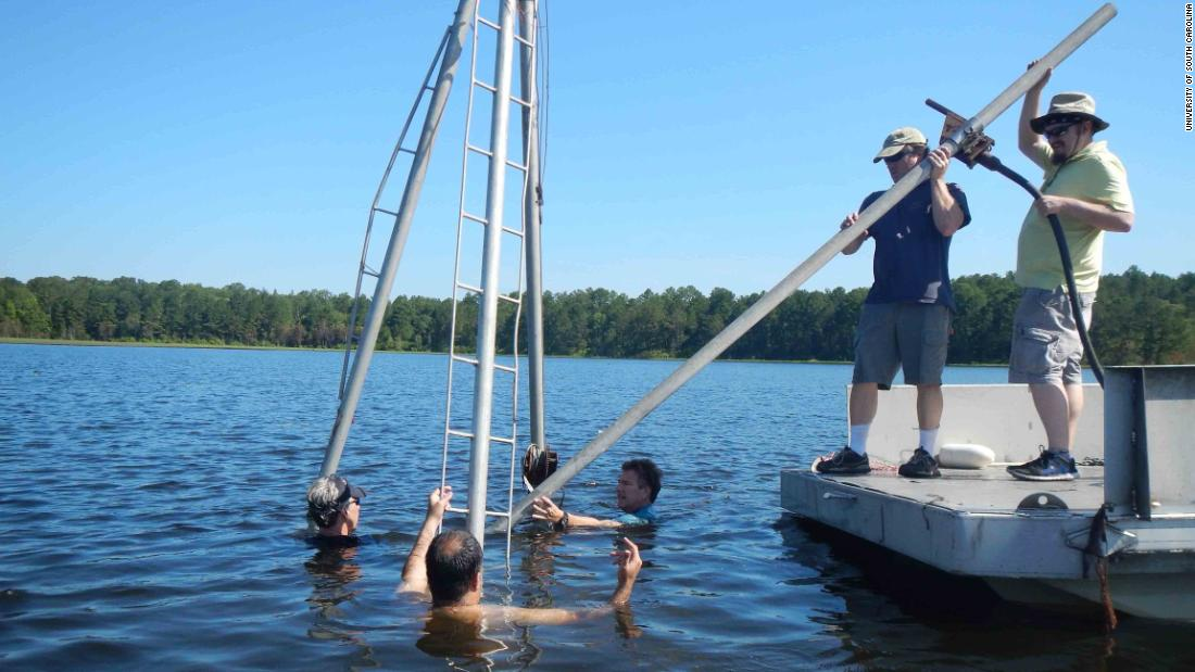 University of South Carolina archaelogist Christopher Moore (second from right) and colleagues collect core samples from White Pond near Elgin, South Carolina, to look for evidence of an impact from an asteroid or comet that may have caused the extinction of large ice-age animals such as sabre-tooth cats and giant sloths and mastodons.