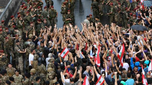 Anti-government protester wave national flags and shout slogans as Lebanese army soldiers face them in the area of Jal al-Dib in the northern outskirts of the Lebanese capital Beirut, on October 23, 2019. - A week of unprecedented Lebanese street protests against the political class showed no signs of abating today, despite the army moving to reopen key roads.