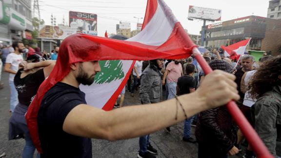 A Lebanese protester uses a national flag to protect himself from the rain on October 23, 2019, in the area of Zouk Mosbeh north of the capital Beirut. - Tens of thousands of Lebanese protesters kept the country on lockdown, rallying for a sixth consecutive day to demand new leaders despite the government