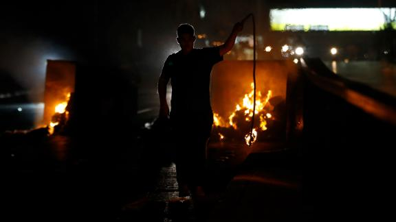 A supporter of Lebanese Prime Minister Saad Hariri burns garbage containers to block a main road in Beirut, Lebanon, Tuesday, Oct. 29, 2019.