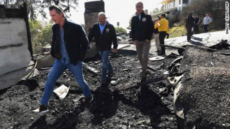 From left, Gov. Gavin Newsom, Los Angeles City Councilman Mike Bonin and Mayor Eric Garcetti tour a burned home Tuesday.
