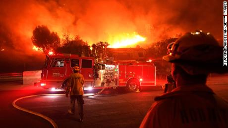 Los Angeles County firefighters look on as the out-of-control Woolsey Fire explodes behind a house in the West Hills neighborhood.
