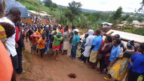 Rescue workers carry a body from the rubble of the landslide in Bafoussam