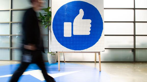 "A Facebook employee walks by a sign displaying the ""like"" sign at Facebook's corporate headquarters campus in Menlo Park, California, on October 23, 2019. (Photo by Josh Edelson / AFP) (Photo by JOSH EDELSON/AFP via Getty Images)"
