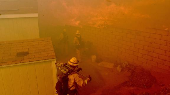 Flames approach the backyards of mobile homes in Jurupa Valley, California, on October 30.