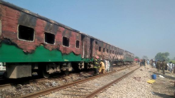 Pakistani officials examine a train damaged by a fire in Liaquatpur, Pakistan, Thursday, Oct. 31, 2019. A massive fire engulfed three carriages of the train traveling in the country