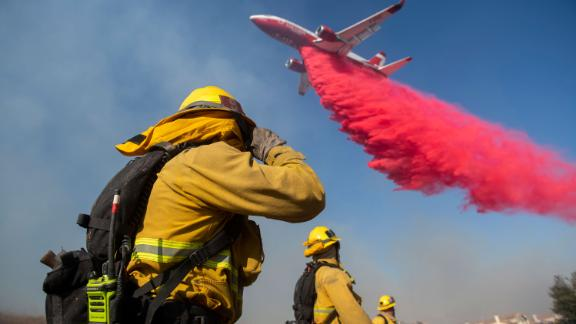 Firefighters brace themselves for incoming fire retardant as they battle the Easy Fire in Simi Valley.