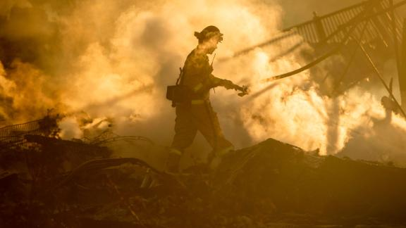 A firefighter sprays down the smoldering remains of a burning home in San Bernardino, California, on Thursday, October 31. It was affected by the Hillside Fire.