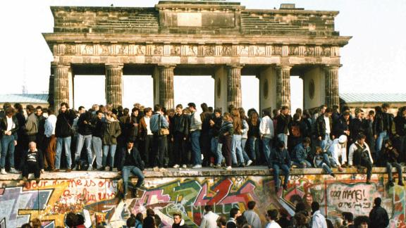 People walk on the Berlin Wall in front of the Brandenburg Gate on November 10, 1989.