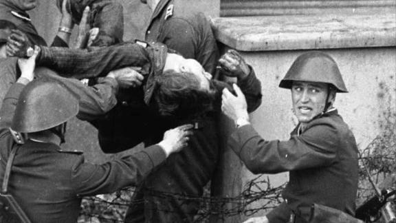 East German bricklayer Peter Fechter, 18, is carried away by border guards after being shot and fatally wounded while attempting to flee to the West in August, 1962. Almost 200 people were killed attempting to cross the Wall between 1961 and 1989.